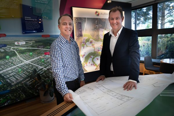 Sunshine Mitre 10 general manager Neil Hutchins with Stockland Senior Economic Development Manager Matthew Byrne reviewing plans for the Aura Business Park - photo by Reflected Image PR